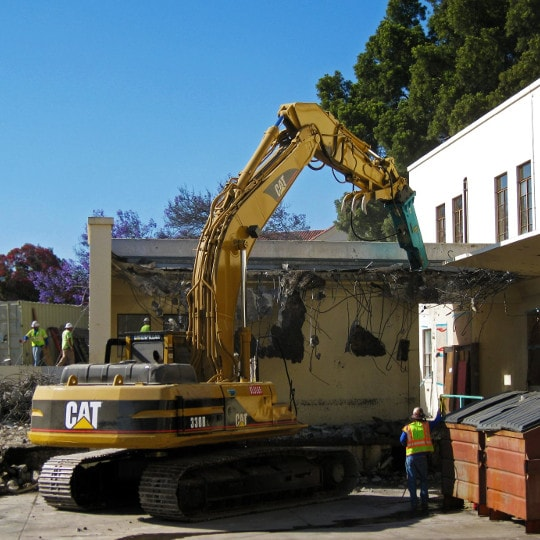excavator demolishing building
